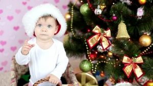 stock-footage-laughing-baby-in-santa-hat-standing-in-a-basket-near-the-christmas-tree-and-gifts